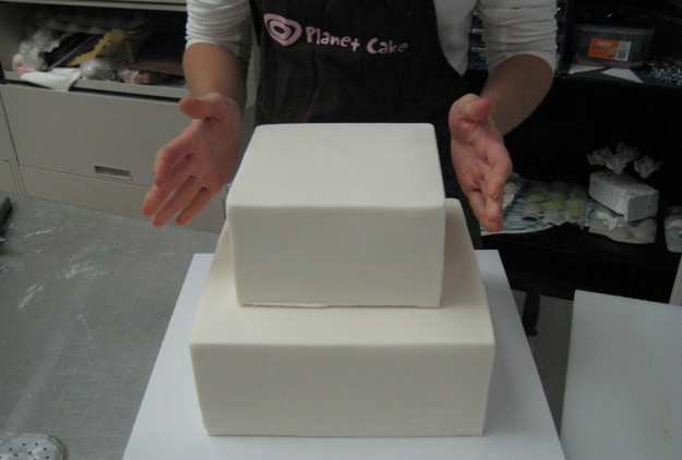 Placing top tier of magnolia cake - Talk Sweet to Me